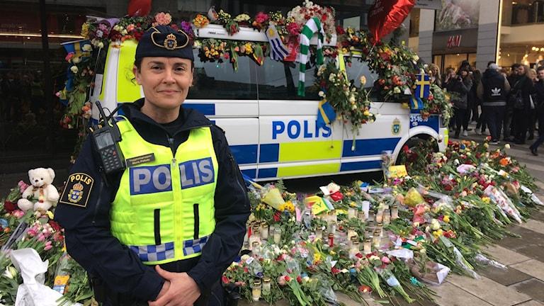 Polis framför en polisbuss täckt med blommor