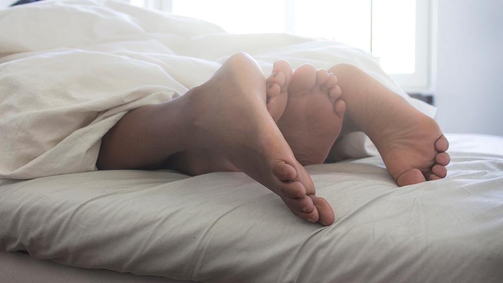 Två par fötter under ett täcke.