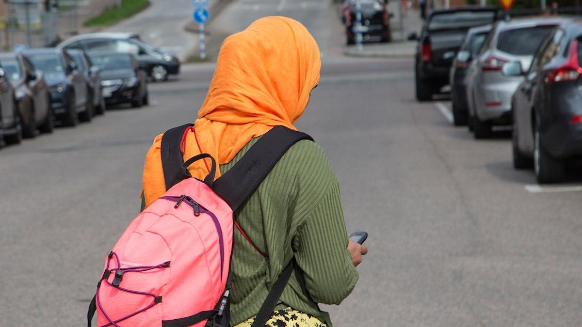 Kvinna med slöja promenerar på gata med mobil i handen.