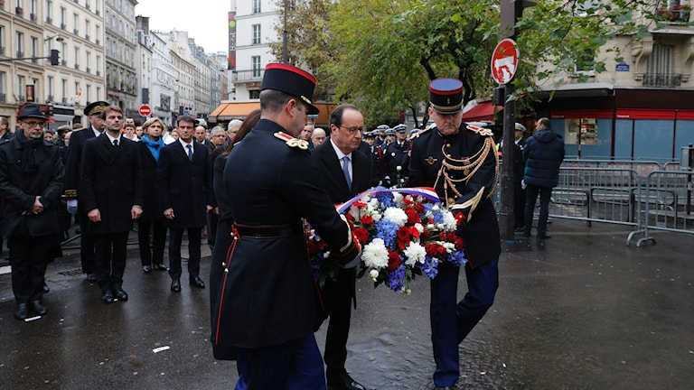 Den franske presidenten Hollande lägger en blombukett  framför ett minnesmärke för terrorattentatens offer i Paris.