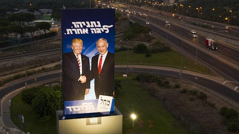 President Donald Trump och israeliske premiärministern Benjamin Netanyahu skakar hand på affisch.