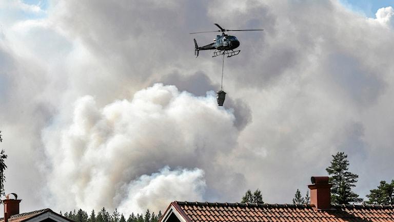 En helikopter hjälper till med släckningsarbetet vid en skogsbrand nära Färila, Ljusdal