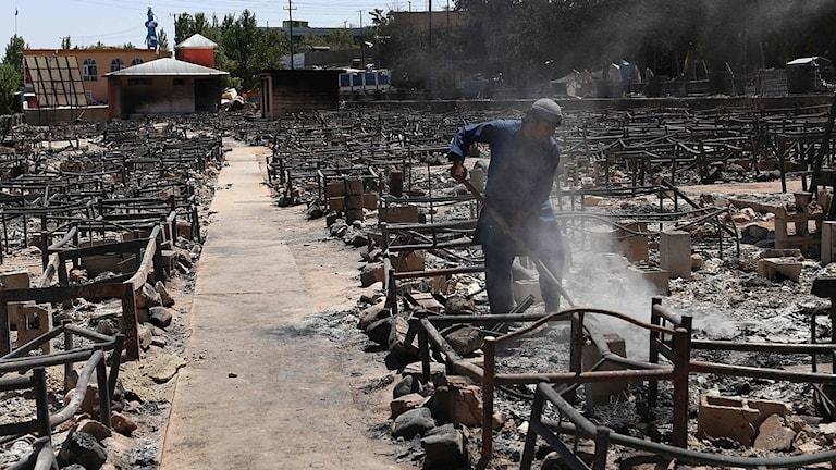 Man skyfflar bort rester efter att talibanerna bränt ner en marknad.