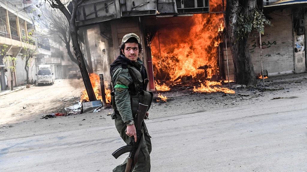En beväpnad man går framför en brinnande butik i staden Afrin