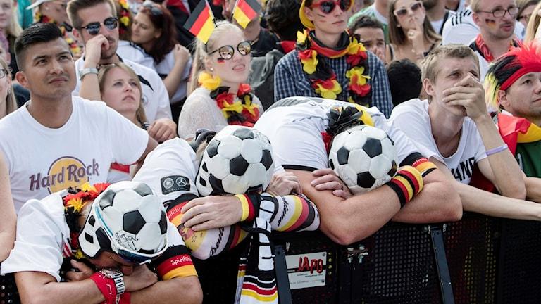 Tyska fotbollsfans i Berlin med fotbollskepsar hänger över ett staket i besvikelse.