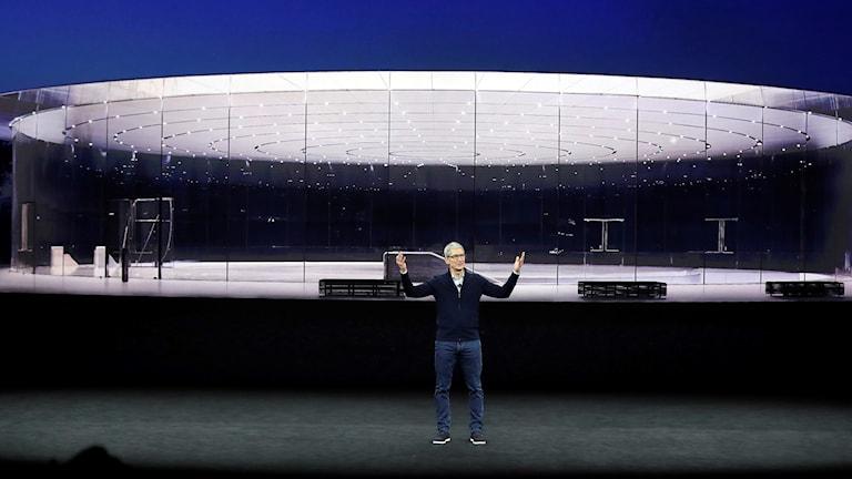 En man står på en scen framför en stor skärm.