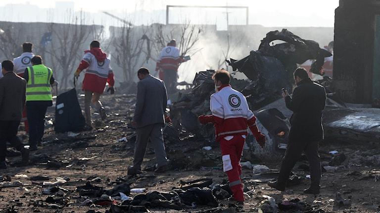 Räddningspersonal vid platsen där planet i Iran kraschade