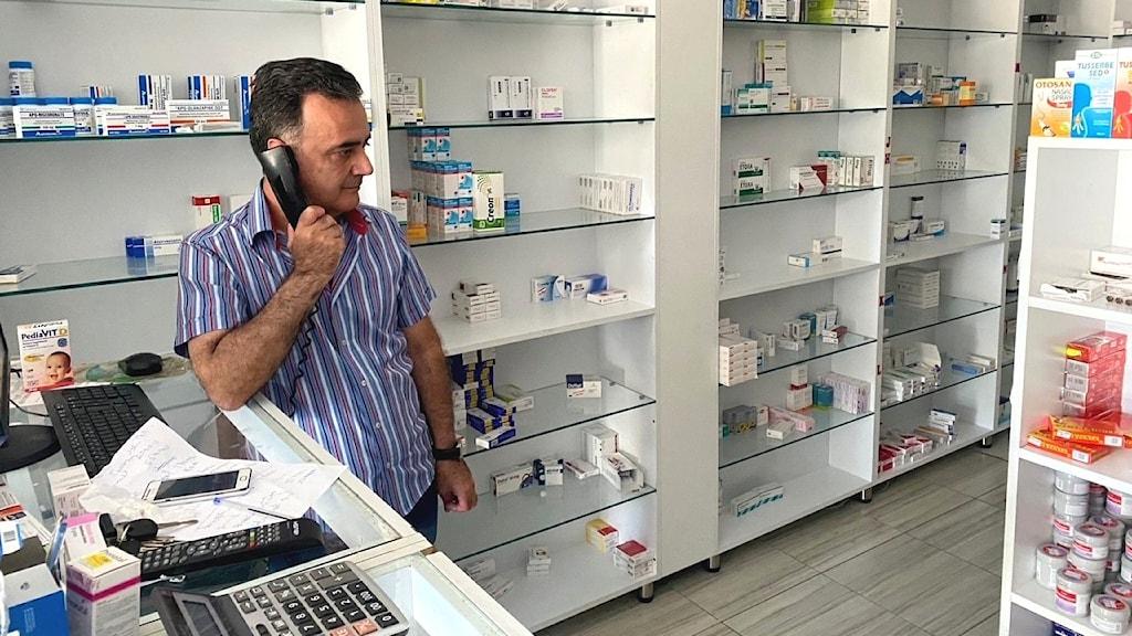 Man bakom disk på apotek håller en telefonlur mot örat.