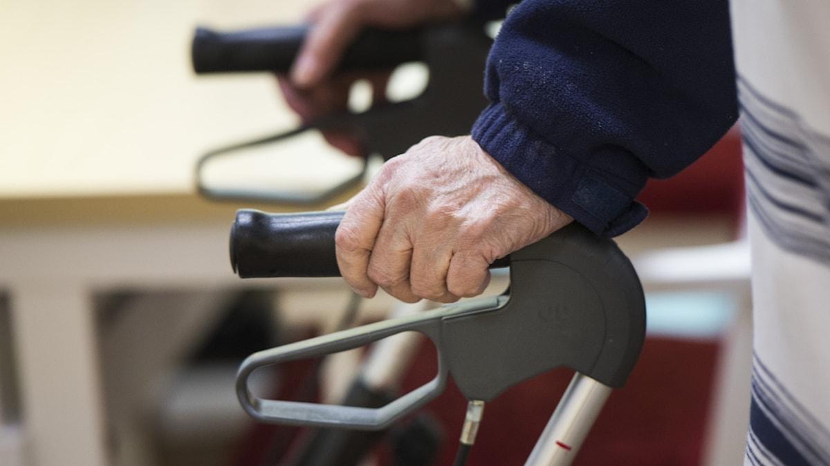 Händerna på en äldre person som håller i rullator.
