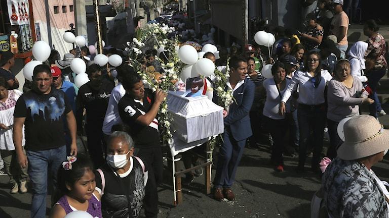 Kistan från den sjuåriga flickan som mördats följt av folkmassor.
