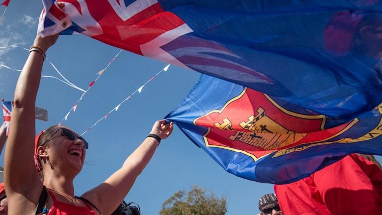 Firande vid Gibraltars nationaldag, människor som håller flaggor i händerna.