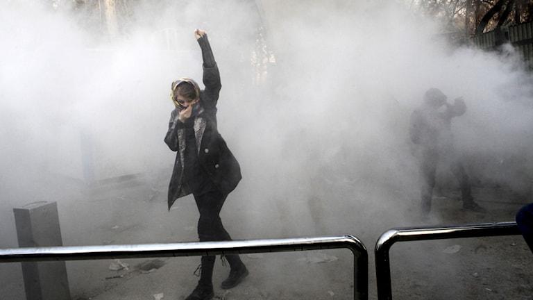 En kvinna i Teheran möts av tårgas under förra årets demonstrationer mot regeringen.