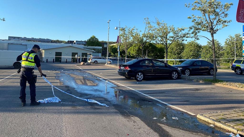 Polis samlar upp polisavspärrningsband på parkeringsplats.