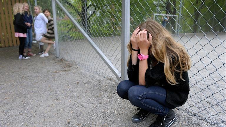 En flicka sitter med händerna framför huvudet, hon är ledsen. Längre bort står ett gäng tjejer och fnissar åt henne.