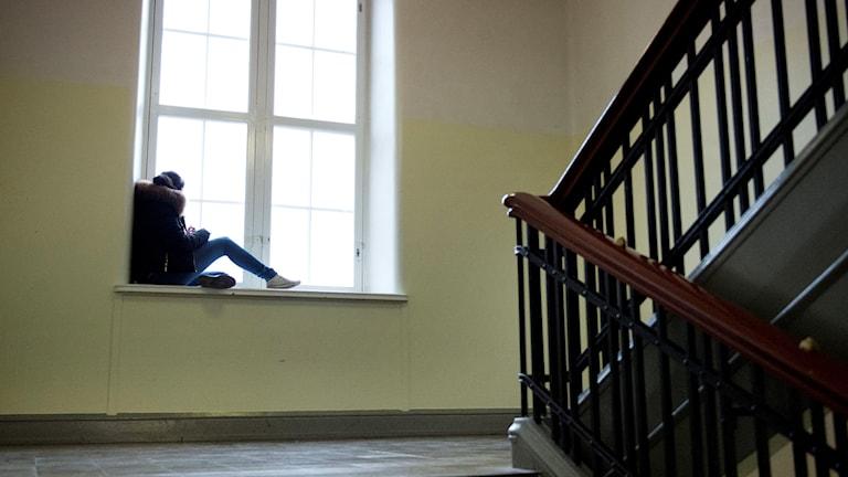 En tonåring sitter ensam i fönster.