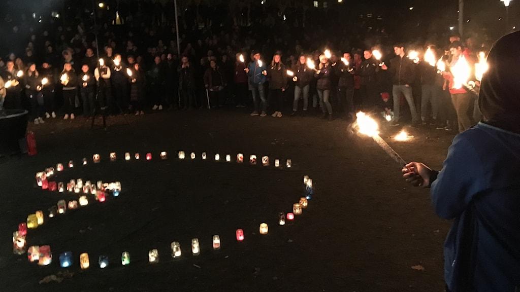 Cirkel av människor med facklor i kvällsmörker, i mitten utställda gravljus i form av ett hjärta.