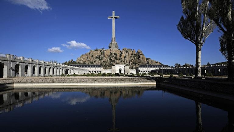 Stort kors på mausoleum framför blankt vatten.