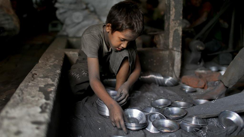 Ung pojke sitter och tillverkar plåtskålar.