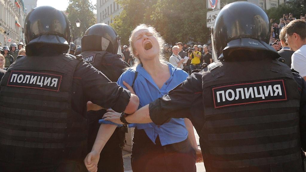 Kvinna som skriker och blir bortförd av polis.