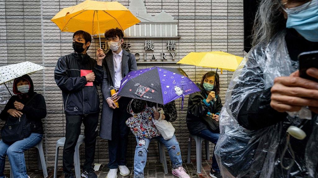 Personer med paraplyer längs med husvägg på gata i Hongkong.