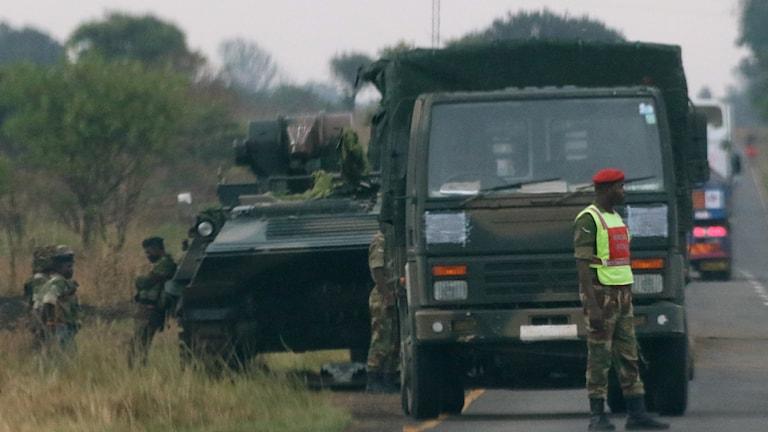 Soldat framför en militär lastbil.