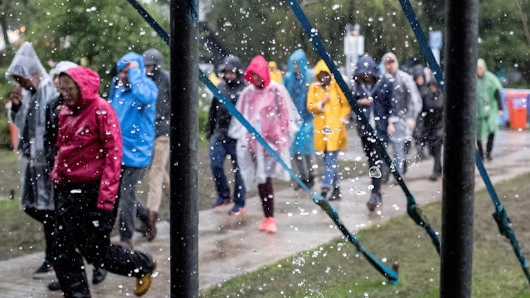 Människor promenerar i regn under festivalen Way Out West.