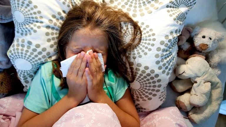 En flicka ligger i sängen med en näsduk över ansiktet.