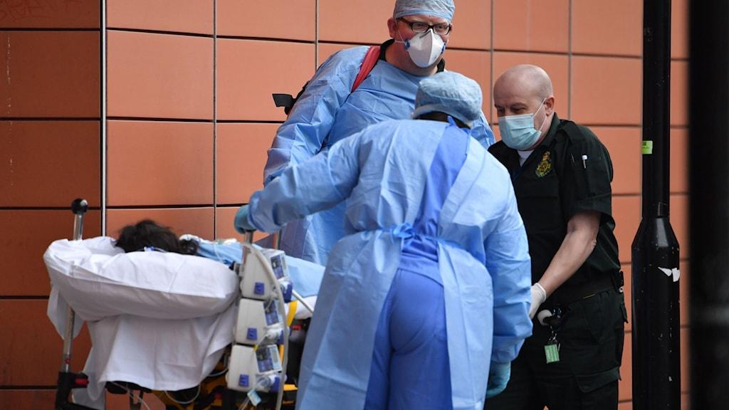 Ambulanspersonal tar omhand en covidpatient utanför Royal London Hospital