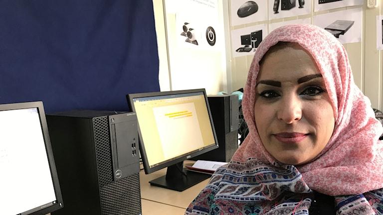 Kvinna framför datorer.