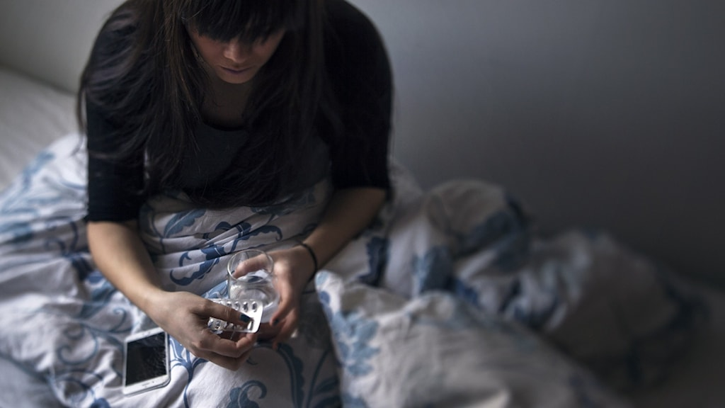 Kvinna i säng håller en karta med mediciner.