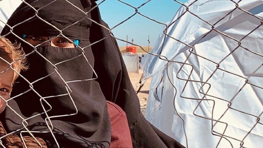 En kvinna med ett barn i flyktinglägret Al-hol.