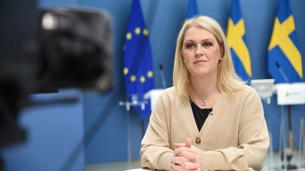 Lena Hallengren står vid bord framför en kamera.