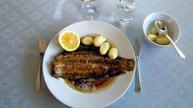 Tallrik med stekt fisk på en restaurang.