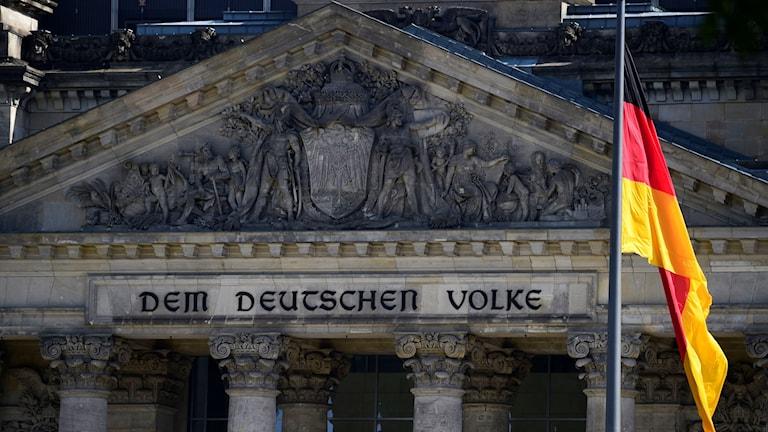 Hus med texten Dem Deutchen volke och en tysk flagga utanför.