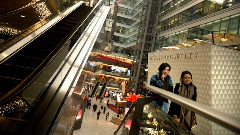 Människor åker rulltrappa i ett köpcentrum i Kina.