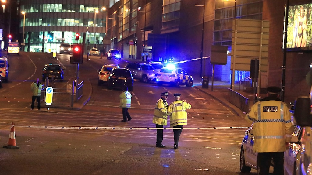 Gatubild med poliser och räddningsmanskap