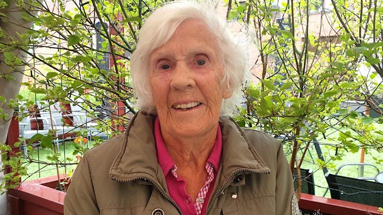 Äldre kvinna på innergård.