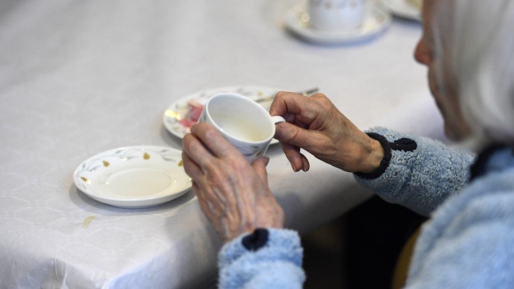 En kvinna håller i kaffekopp på ett äldreboende.