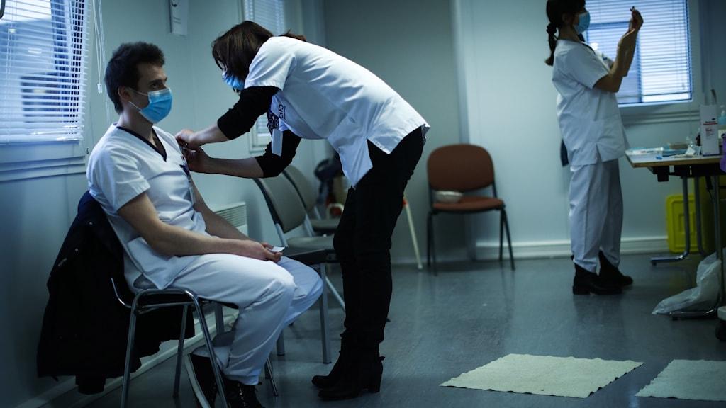 En man i sjukhuskläder får en spruta i armen.