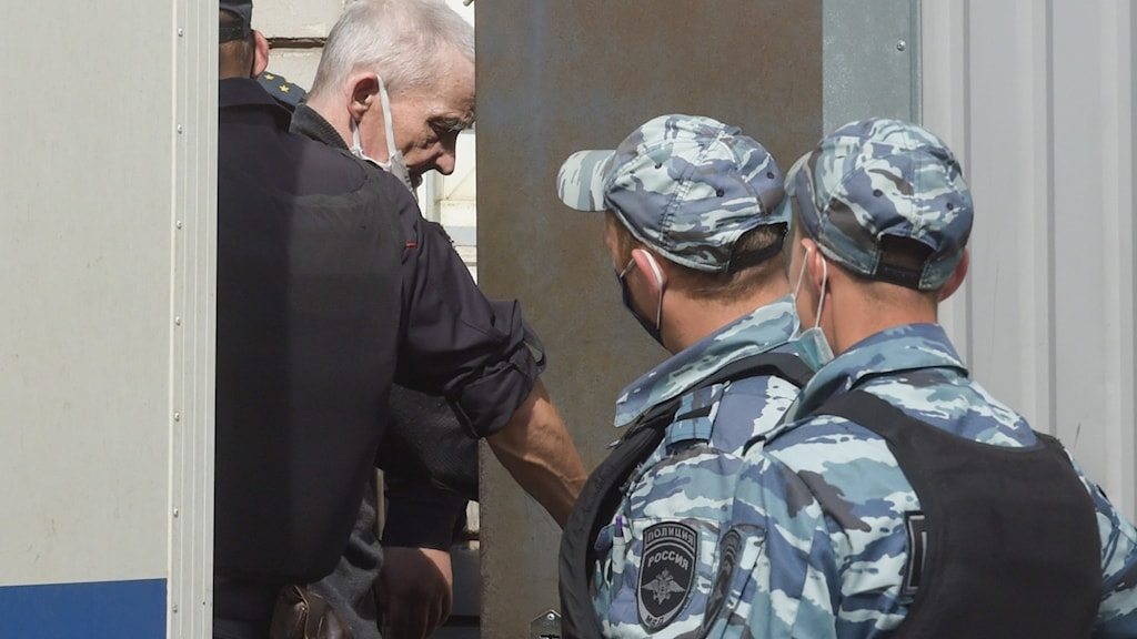 Jurij Dmitrijev eskorteras av polis