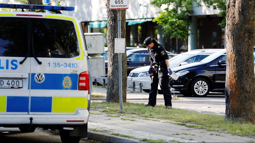 Polis inspekterar ett område vid en parkering.