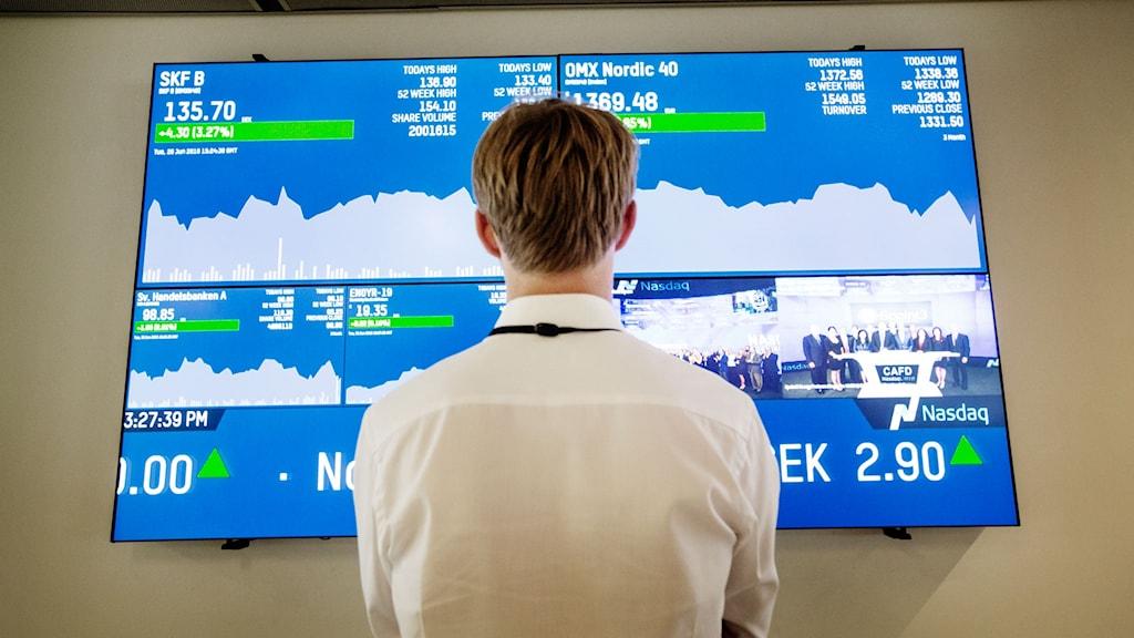 Man tittar på skärm med börsnoteringar. Arkivbild från Stockholmsbörsen.