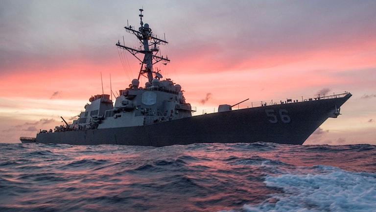 Krigsfartyg mot färgstark himmel