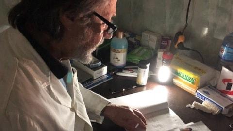 Den pensionerade italienske barnläkaren Marino Andolina arbetar i ficklampans sken.