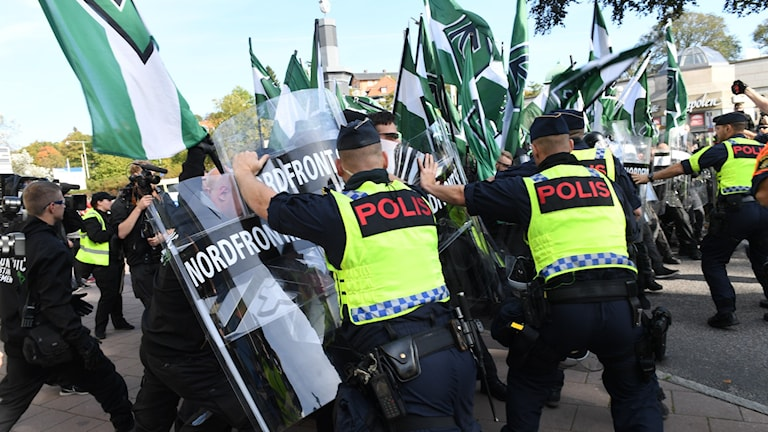 Poliser blockerar demonstranter från NMR som har grönvita flaggor.