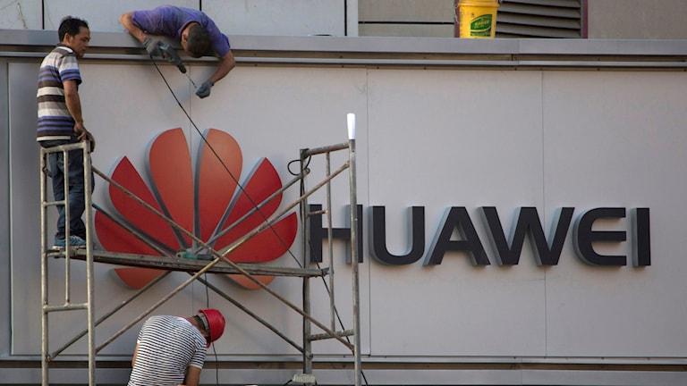 Personer står på en byggnadsställning bredvid Huaweis logga.