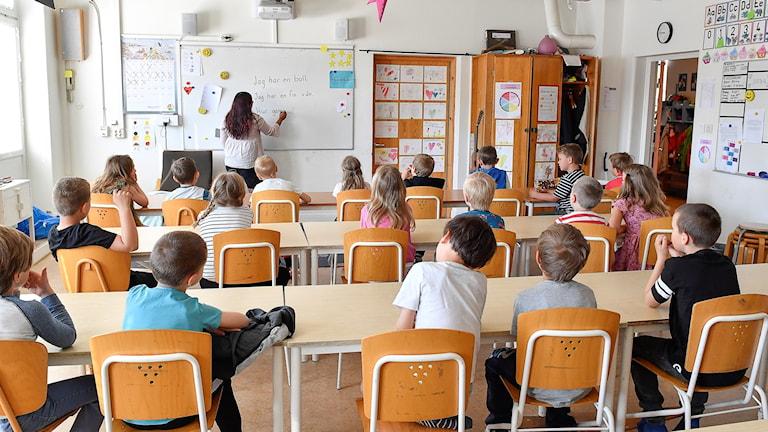 Elever i klassrum, lärare skriver på tavlan.