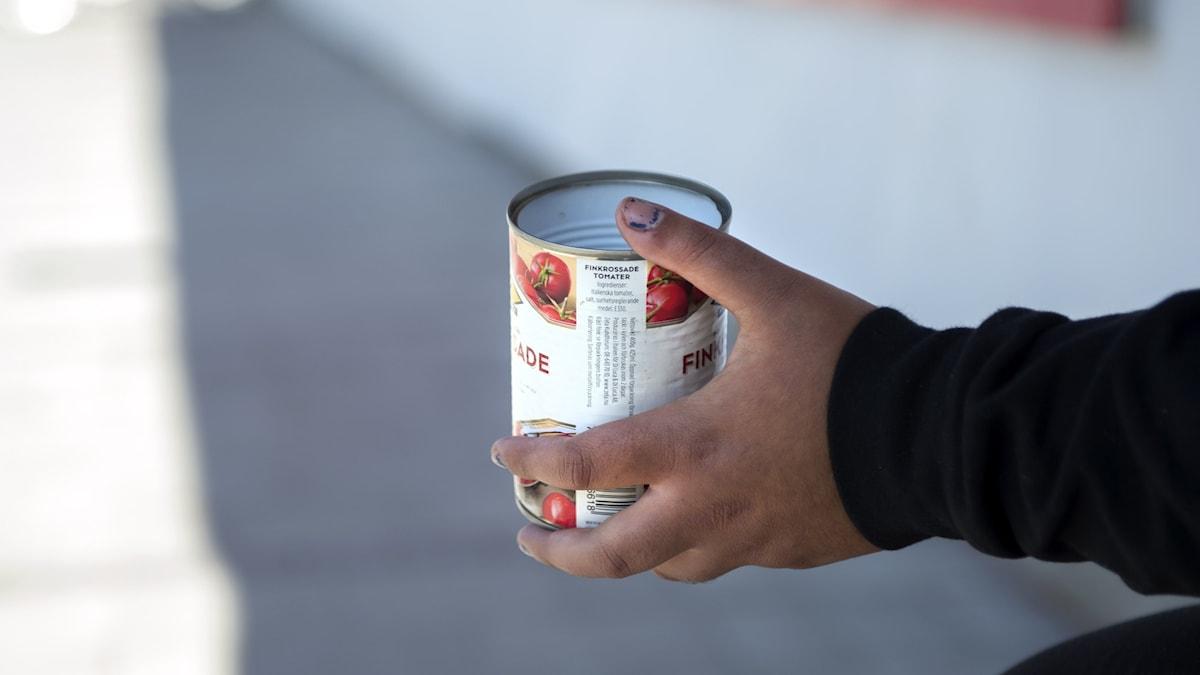 En person sticker fram en tom konservburk för att tigga pengar.