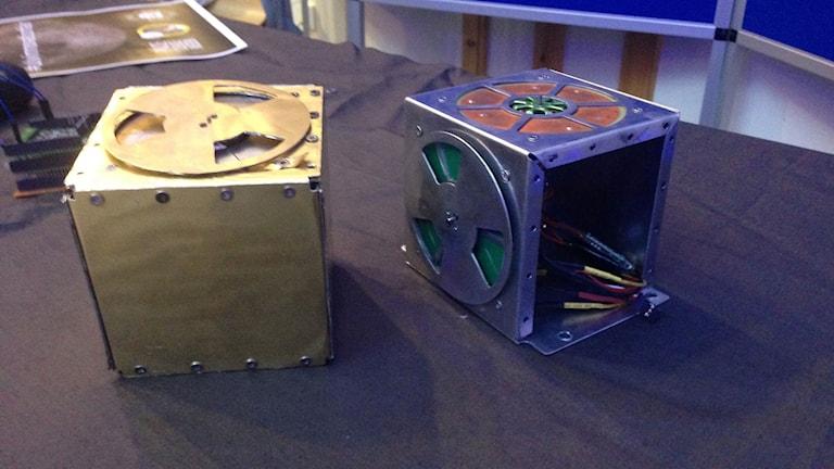 Två fyrkrantiga lådor på ett bord. En är av ljust trä och en är lila.
