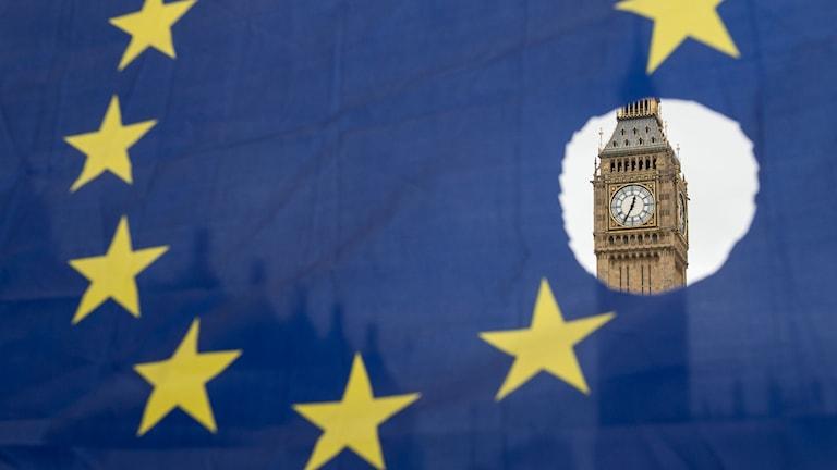 EU-flagga med en stjärna bortskuren och genom hålet ser man Big Ben.